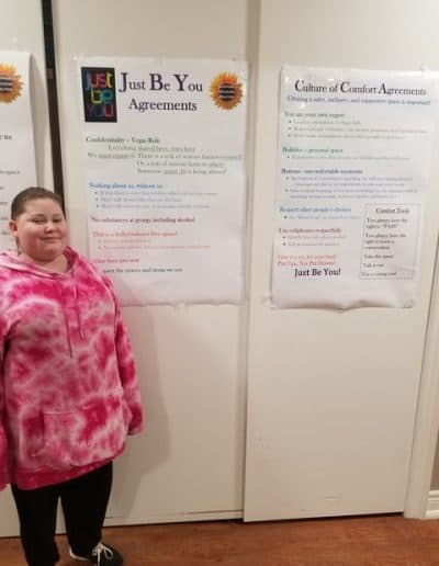 Youth standing in front of the Just Be You Agreements poster on the wall.