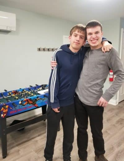 Two youth smiling in front of a foosball table during Just Be You.