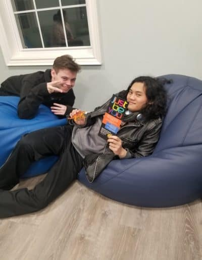 2 youth relaxing on bean bag chairs during Just Be You.