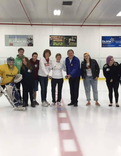 Michele Sparling and others pose for a photo on the ice.