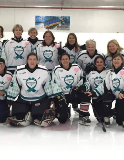 Group of hockey players from the hockey tournament smiling on the ice.