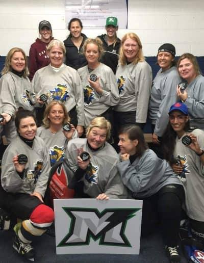 Markham Thunder women holding hockey pucks for the camera in the hockey locker room.