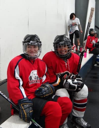 Two women hockey players smiling in their red jerseys.